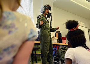 Capt. Nicolas DeWulf, 510th Fighter Squadron pilot, demonstrates his flying gear to 2nd grade students during the STEMposium at the Aviano Elementary school. - Photo DoD